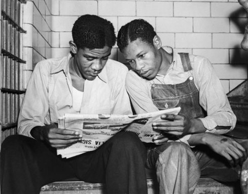 In this July 16, 1937 file photo, Charlie Weems, left, and Clarence Norris, Scottsboro case defendants, read a newspaper in their Decatur, Ala. jail after Norris was found guilty for a third time by a jury which specified the death penalty. Weems was to be tried a week later. Nine black teenagers known as the Scottsboro Boys were convicted by all-white juries of raping two white women on a train in Alabama in 1931. All but the youngest were sentenced to death, even though one of the women recanted her story. All eventually got out of prison, but only one received a pardon before he died. (AP Photo)