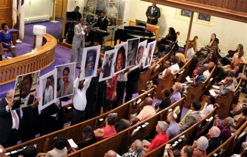 In this photo taken June 19, 2015, photos of the victims of the shooting at Emanuel AME Church in Charleston, S.C., are held during a vigil at the Metropolitan African Methodist Episcopal Church in Washington. The black church has long been the cornerstone and sanctuary for African American life. It has also long been a target for racists and white supremacists trying to strike blows against the African American psyche. The latest attack came Wednesday in Charleston, South Carolina, when 21-year-old Dylann Storm Roof joined a prayer meeting inside historic Emanuel African Methodist Episcopal Church and shot nine people dead, including the pastor, the Rev. Clementa Pinckney, and other ministers. (AP Photo/Glynn A. Hill)